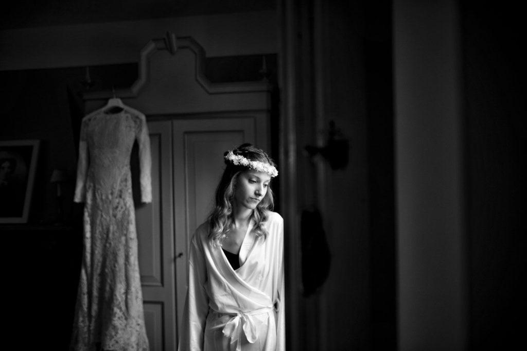un ritratto in bianco e nero della sposa con alle spalle l'abito in pizzo